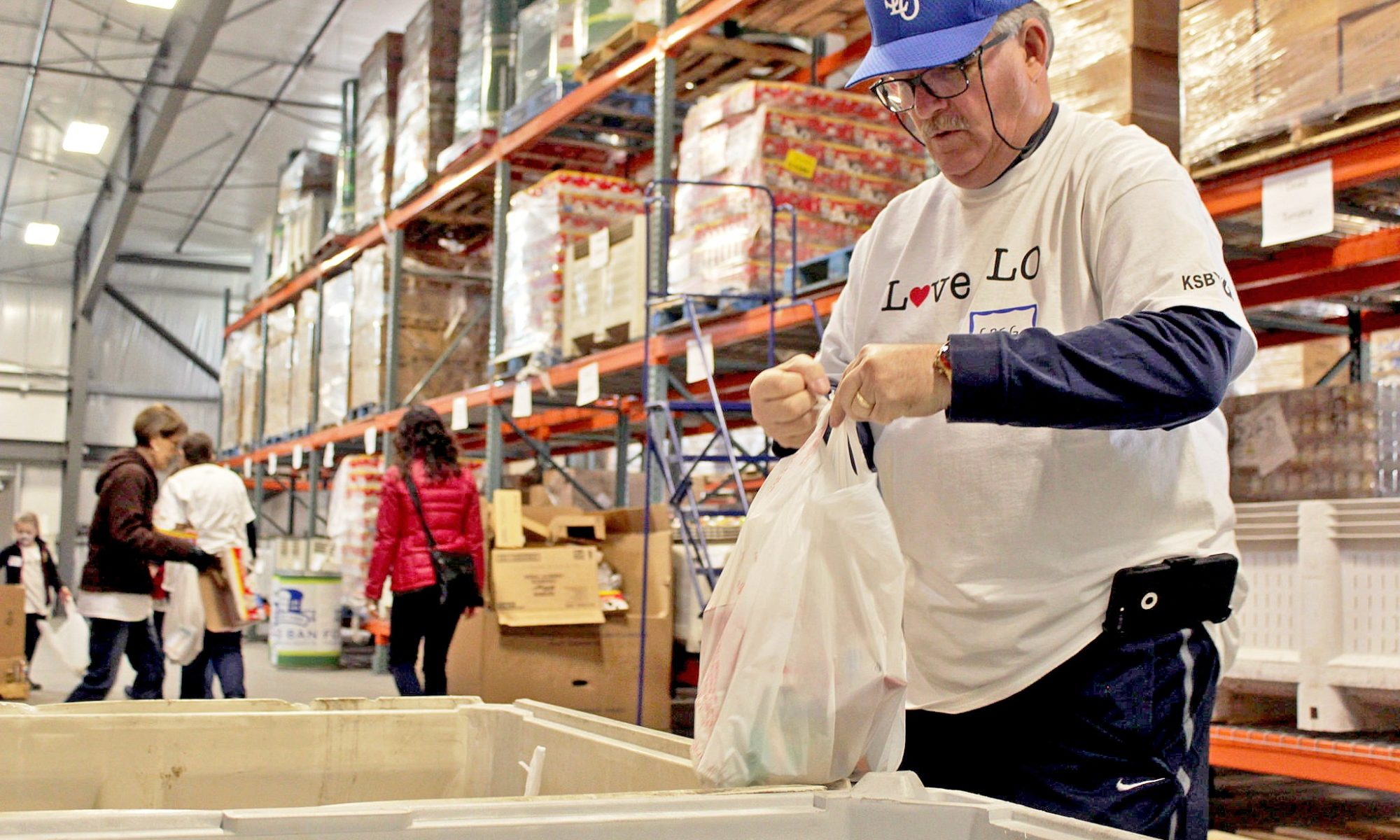 a man in a whote shirt placing food items in a white plastic bag for distribution